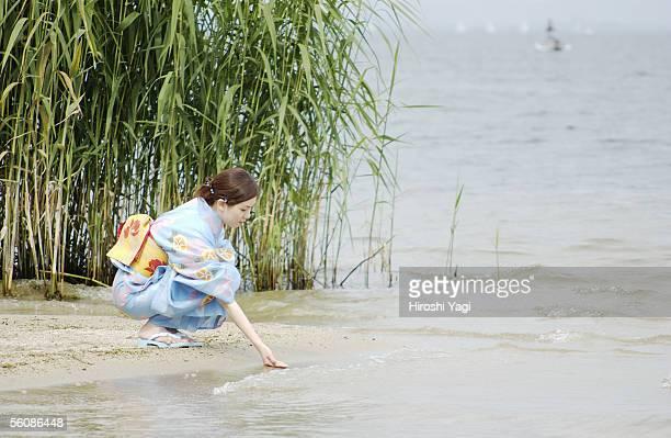 A young woman in kimono touching water