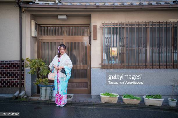 young woman in kimono traditional japanese clothes standing front of a house