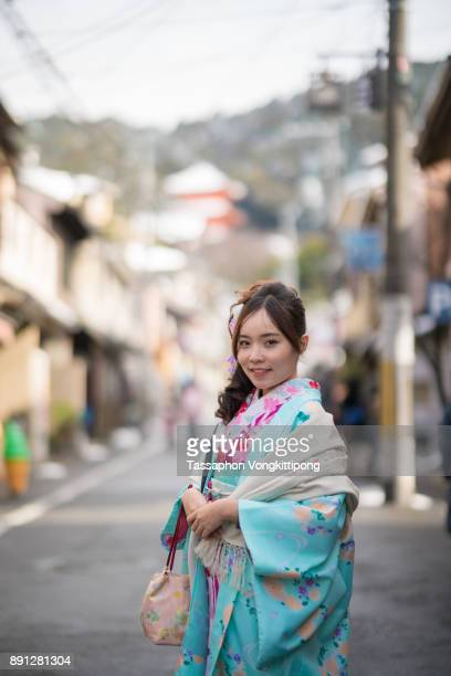 young woman in kimono traditional japanese clothes standing in the road