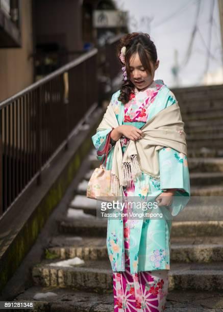 young woman in kimono walking down a stair