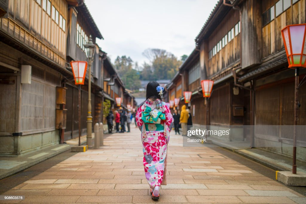 Young woman in kimono walking in traditional Japanese town : Stock Photo