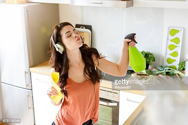 young woman in kitchen cleaning and listening to music - きれいにする ストックフォトと画像