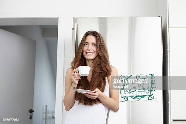 Young woman in kitchen drinking cup of coffee