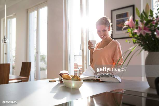 Young woman in kitchen having breakfast in kitchen, paging through book