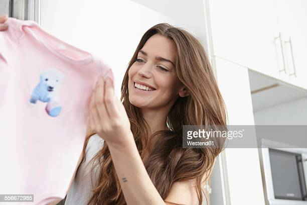 Young woman in kitchen holding pink baby sleepers