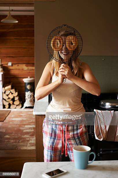 young woman in kitchen holding up bagels - four people photos et images de collection