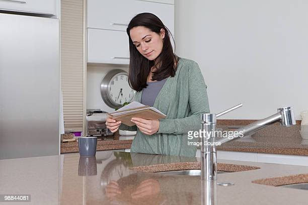 Young woman in kitchen looking at mail