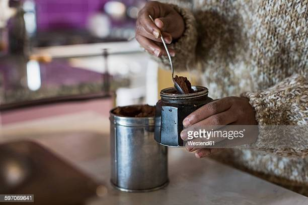 young woman in kitchen preparing coffee - café moulu photos et images de collection
