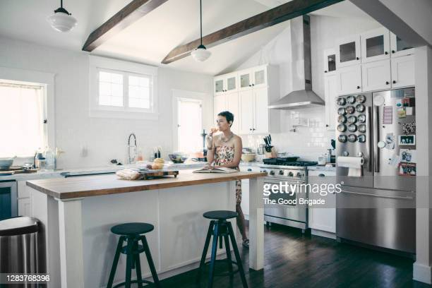 young woman in kitchen sipping a glass of wine - kitchen stock pictures, royalty-free photos & images