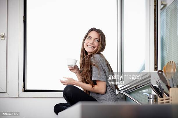 young woman in kitchen sitting at window drinking coffee - one young woman only stock pictures, royalty-free photos & images