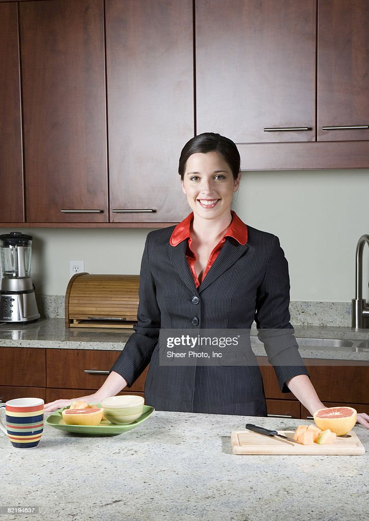 young woman in kitchen with fruit on counter : Stock Photo