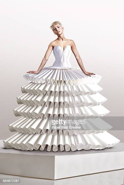 Young woman in large white paper craft dress