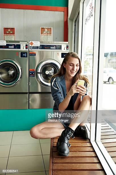 young woman in laundromat - waschsalon stock-fotos und bilder