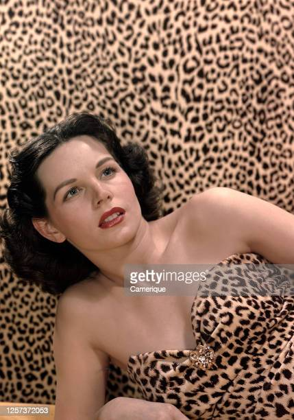 Young woman in leopard skin outfit lounging against matching leopard skin backdrop.