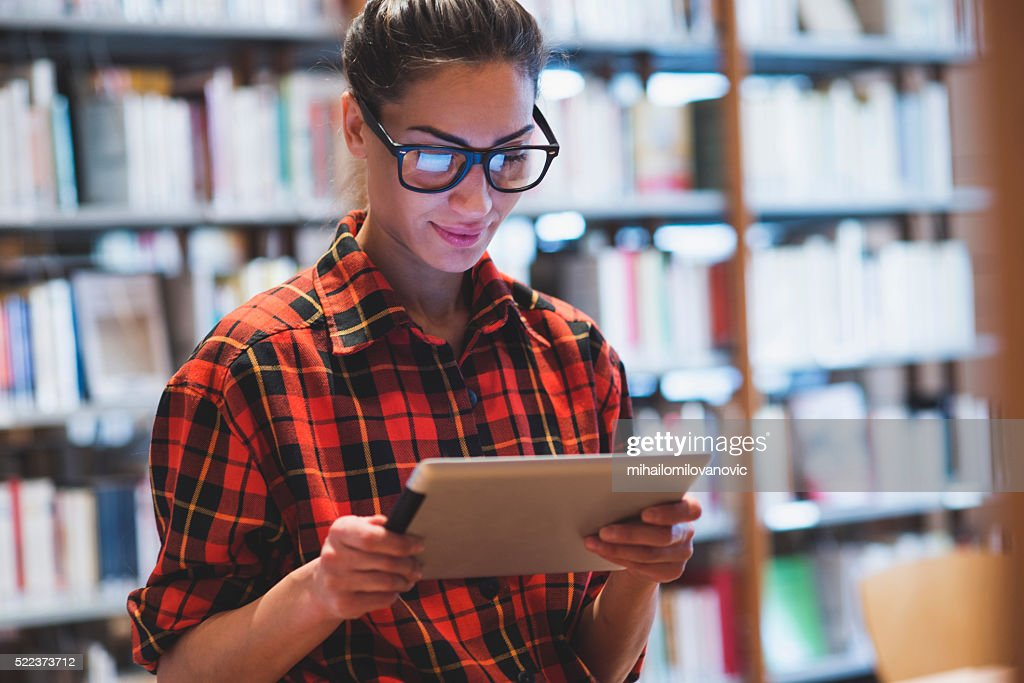 Young woman in library : Stock Photo