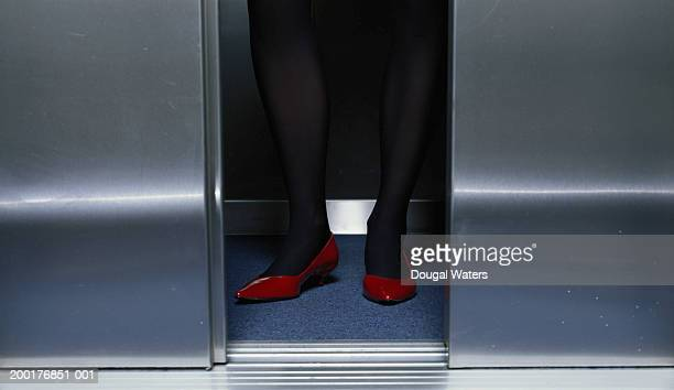 Young woman in lift, view through gap in doors, low section