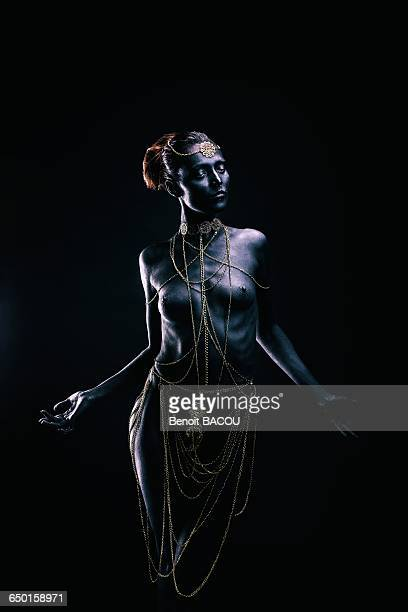 Young woman in light of ethnic ceremony, Length, face, hands on the sides, looking down