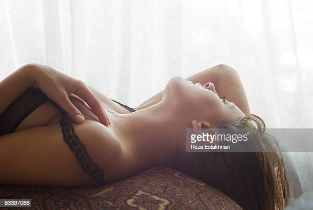 young woman in lingerie lays back on ottoman - erotiek stockfoto's en -beelden