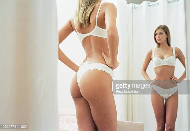 Young woman in lingerie looking at mirror in dressing room