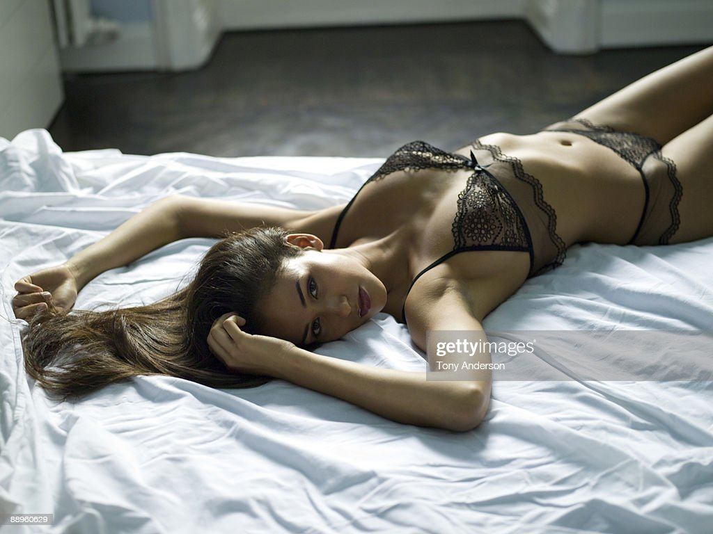 Young woman in lingerie lying on bed : Stock Photo
