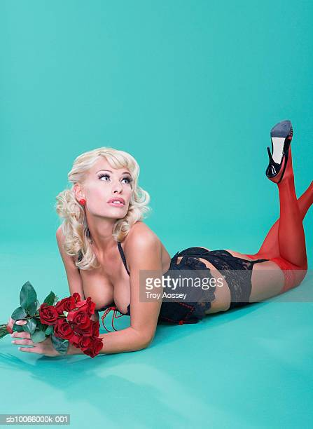 young woman in lingerie, lying on floor, holding bunch of roses - stockings and suspenders - fotografias e filmes do acervo