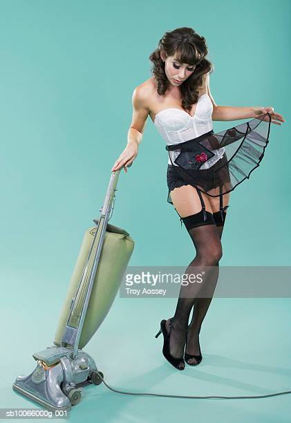 Young woman in lingerie with vacuum cleaner