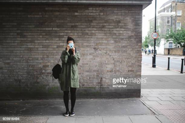 young woman in london standing against the brick wall, taking a photo with analog camera - parka coat stock photos and pictures
