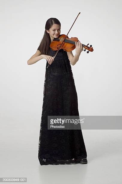 Young woman in long black dress, playing violin in studio