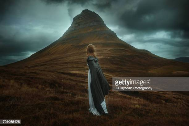 young woman in long dress standing in a field in iceland - wikinger stock-fotos und bilder