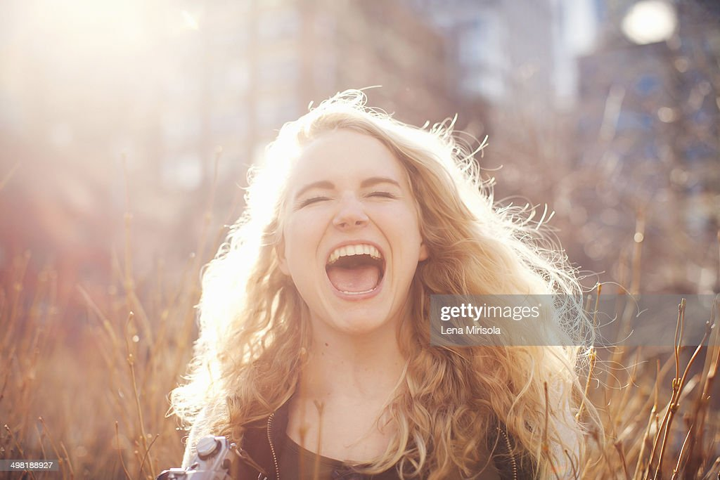 Young woman in long grass with open mouth : Stock Photo