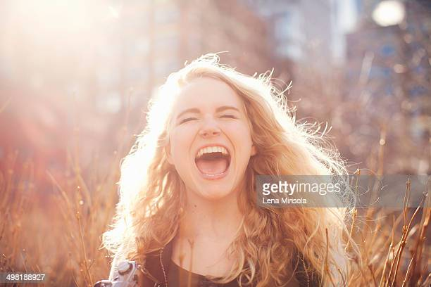 young woman in long grass with open mouth - shouting stock photos and pictures