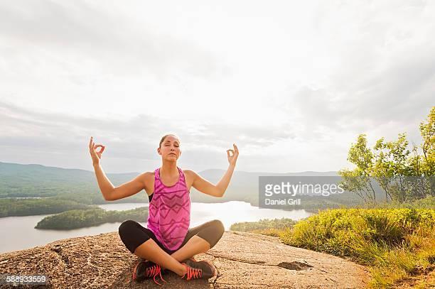 Young woman in lotus position against lake