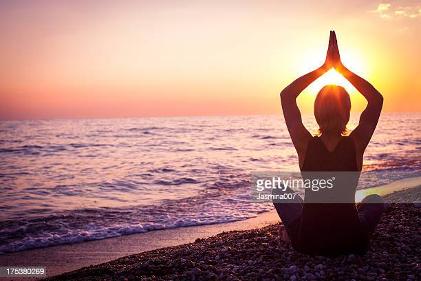 young woman in lotus position meditating at sunset - lotuspositie stockfoto's en -beelden