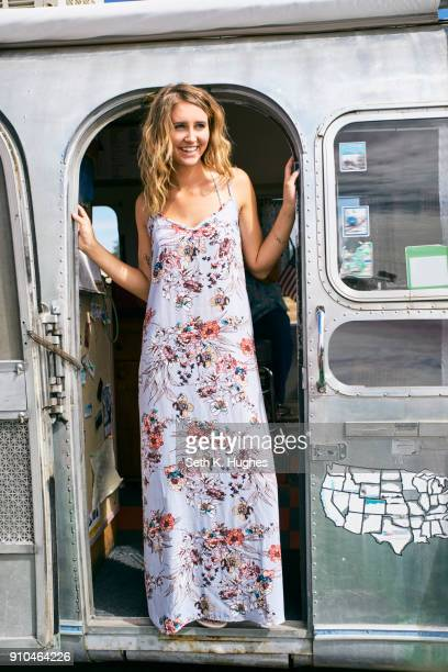 Young woman in maxi dress looking out from airstream doorway