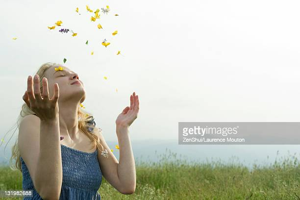 Young woman in meadow, covered in wildflowers