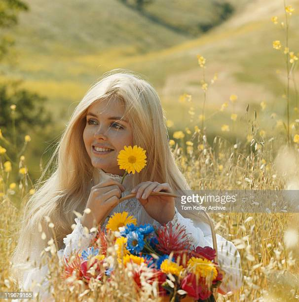young woman in meadow holding flowers of basket, smiling - 1972 stock pictures, royalty-free photos & images