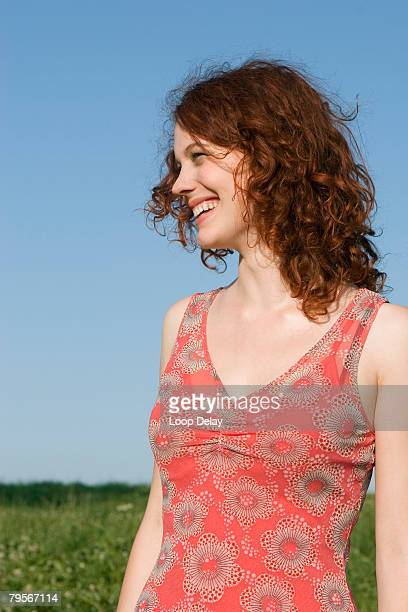 'Young woman standing in meadow, smiling'