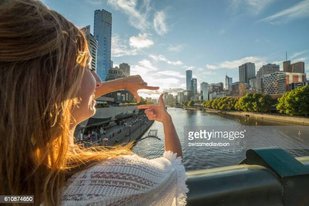 Young woman in Melbourne frames skyline into finger frame