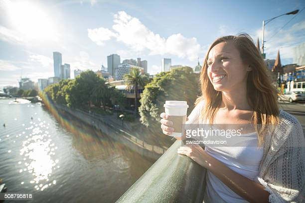 Young woman in Melbourne on bridge overlooks the Melbourne CBD