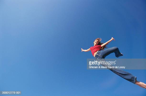 young woman in mid-air against blue sky, portrait (wide angle) - 真下からの眺め ストックフォトと画像