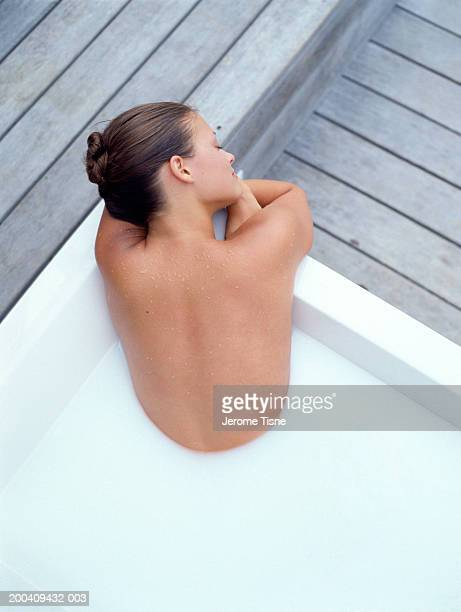 Young woman in milk bath, rear view, elevated view