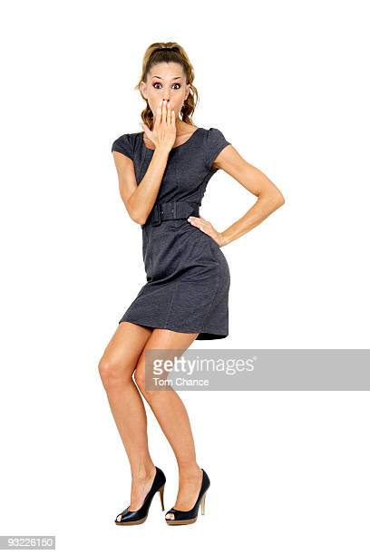 Young woman in mini dress standing with hand over mouth, portrait