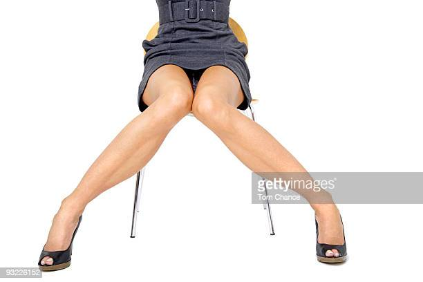 young woman in mini dress sitting on chair, middle section - legs spread woman stock photos and pictures