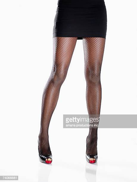 Young woman in mini skirt and stilettos (low section)