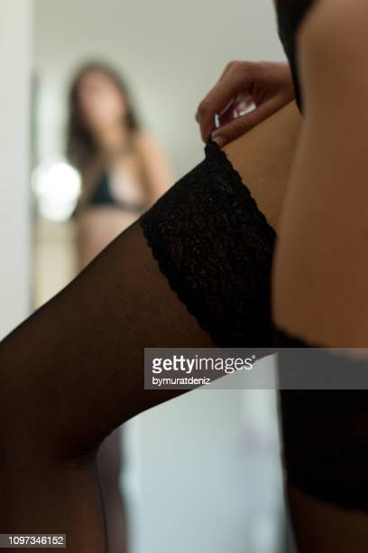Young woman in mirror showing off garter