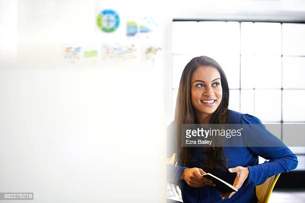 Young woman in modern office smiling and relaxing.