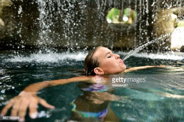 Young woman in natural pool spitting water