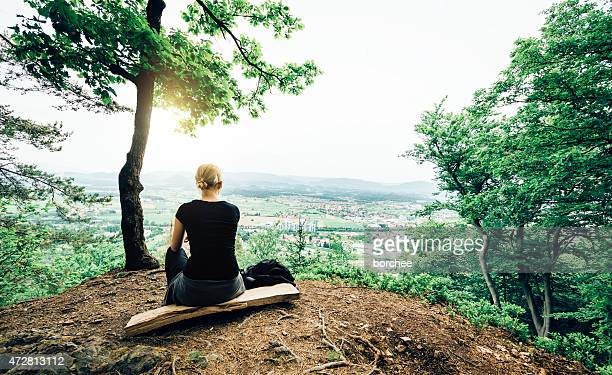 Young Woman In Nature Looking Down On The City