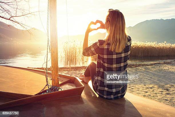 Young woman in nature making heart shape finger frame