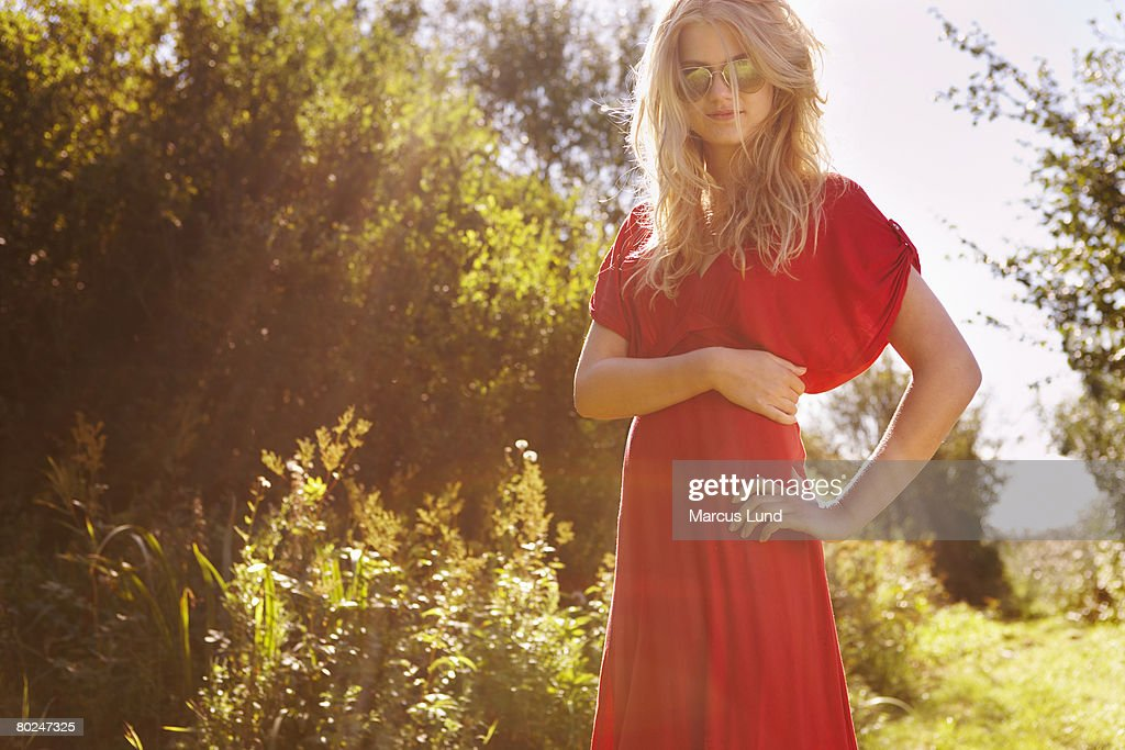 Young woman in nature wearing red dress : Stock Photo